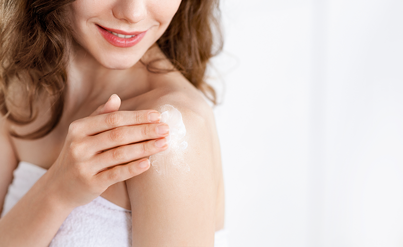 000cropped-of-young-woman-applying-lotion-on-shoulder-GMEA4T3